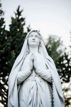 Statue of Mary looking to the sky praying with rosary around her arm